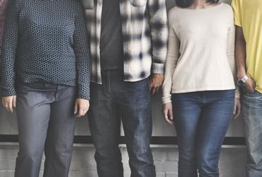 vier Menschen stehen nebeneinander